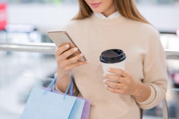 休憩しながらスマートフォンでオンライングッズをスクロールする紙袋とコーヒーのグラスを持つ若い女性