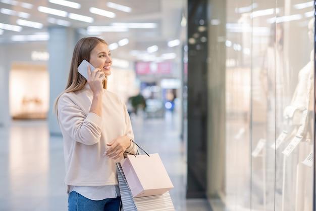 ショーウィンドウで新しいファッションコレクションを見ながら携帯電話で誰かに話している紙袋を持つ若い女性
