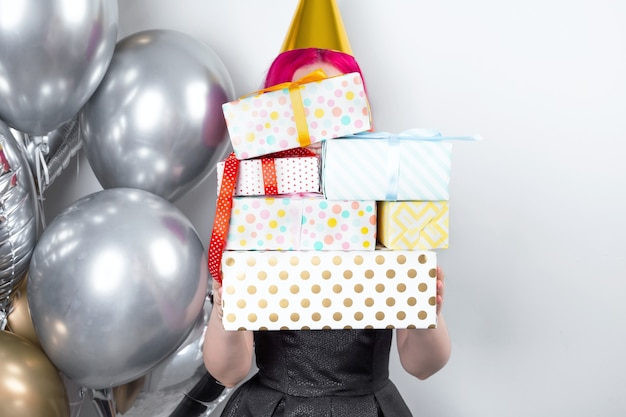 Young woman with party hat holds birthday gifts. nearby gold and silver balloons
