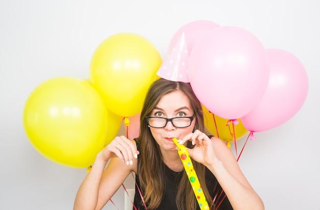 白い背景の上のノイズメーカーとパーティーハットを持つ若い女性。