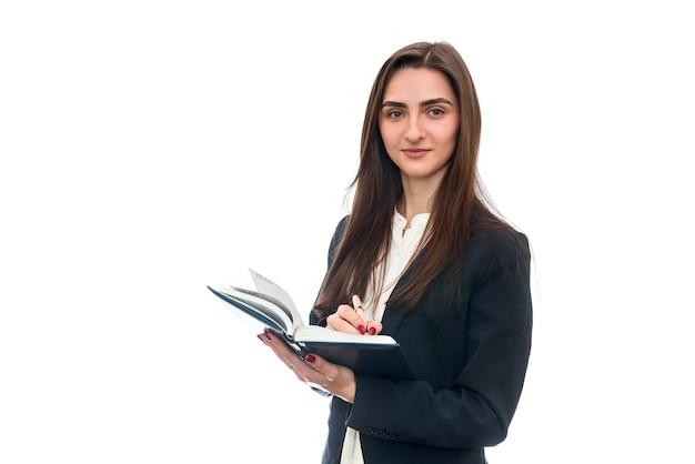 白で隔離のペンと日記を持つ若い女性