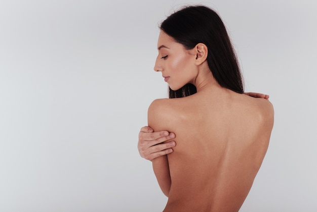 Young woman with perfect body and smooth skin stands with her back on the white wall.