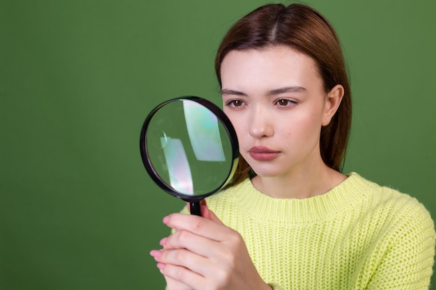 Young woman with perfect natural makeup brown big lips in casual sweater on green wall with magnifier searching