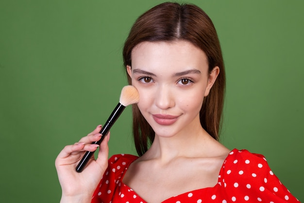 Young woman with perfect natural makeup brown big lips in polka dot red dress on green wall holds blush brush fashion beauty portrait