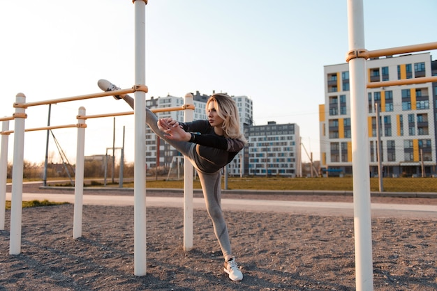 Young woman with perfect sexy body in sportswear trains outdoors on the playground. woman stretching with horizontal bar. healthy lifestyle, sport and exercise concept.