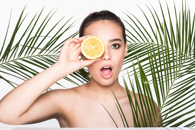 Young woman with perfect skin holding citrus fruit in hand surrounded by palms leaves isolated on white wall