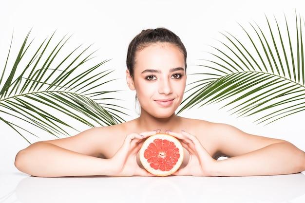 白い壁に分離されたヤシの葉に囲まれた手で柑橘系の果物を保持している完璧な肌を持つ若い女性