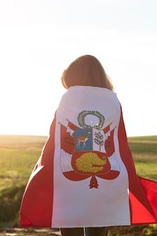Giovane donna con bandiera del perù all'aperto