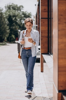通りの外を歩いている電話とコンピューターを持つ若い女性