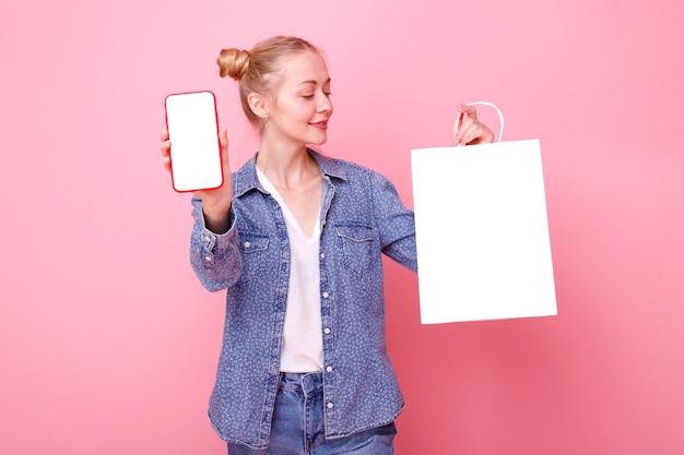 電話とピンクの白いパックを持つ若い女性