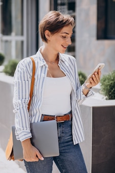 Young woman with phone and computer walking outside the street