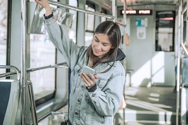 公共交通機関で電話を持つ若い女性。