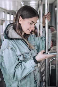 公共交通機関で電話を持つ若い女性