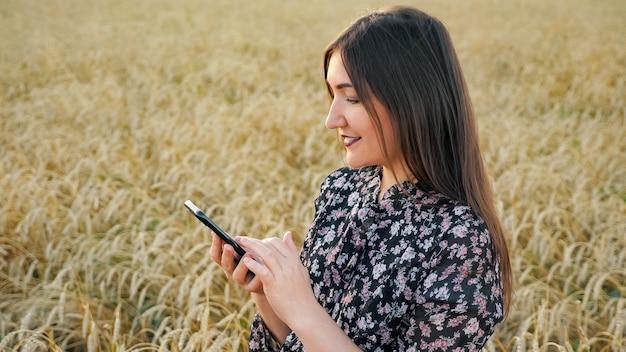 Молодая женщина с телефоном в поле спелой пшеницы.