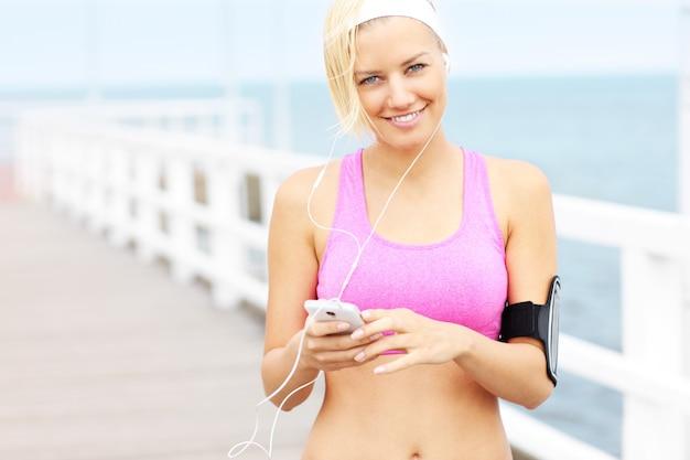 Молодая женщина с телефоном, слушать музыку на пирсе