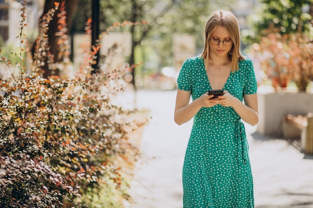通りを歩いて電話を持つ若い女