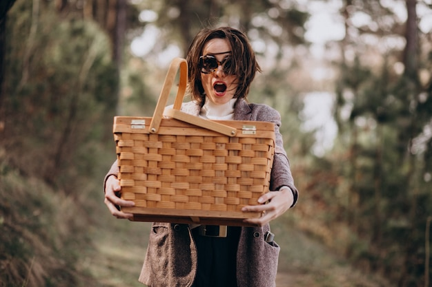 Young woman with picnic box in the forest