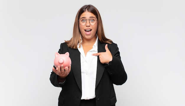 Young woman with a piggy bank feeling happy, surprised and proud, pointing to self with an excited, amazed look