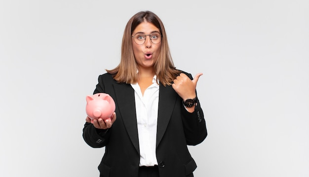 Young woman with a piggy bank looking astonished in disbelief, pointing at object on the side and saying wow, unbelievable