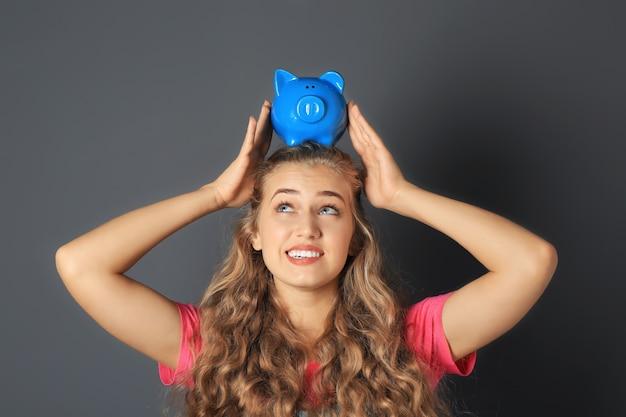 灰色の貯金箱を持つ若い女性