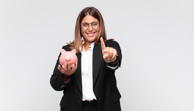 Young woman with a piggy bank smiling proudly and confidently making number one pose triumphantly, feeling like a leader
