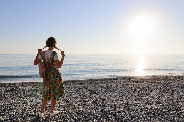 Young woman with pigtails stands with her back alone on stony seashore at sunset