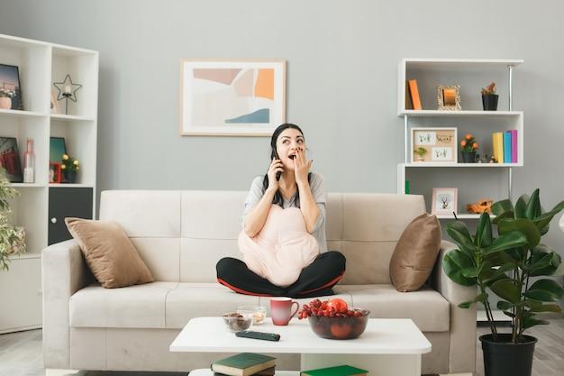 コーヒーテーブルの後ろのソファに座っている枕を持つ若い女性は、リビングルームで電話で話します