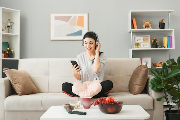 Молодая женщина с подушкой в наушниках держит и смотрит на телефон, сидя на диване за журнальным столиком в гостиной