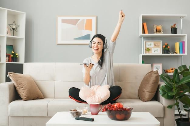 Молодая женщина с подушкой в наушниках держит телефон, сидя на диване за журнальным столиком в гостиной