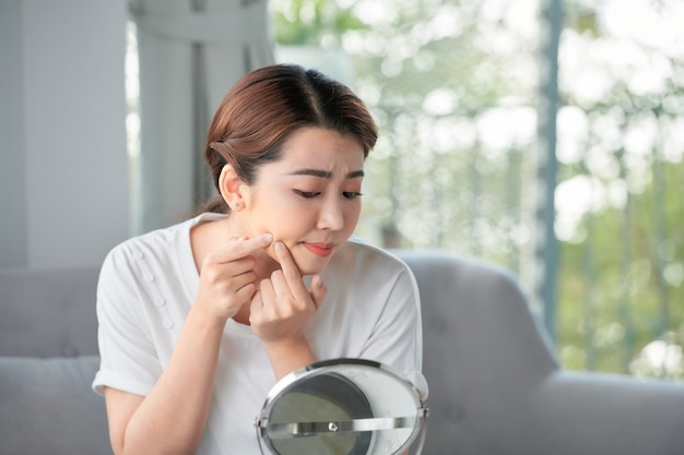 Young woman with pimple on her face