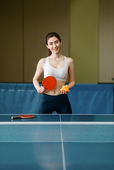 Young woman with ping pong racket and  ball at the table indoors.