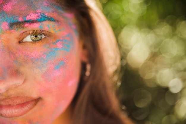Young woman with pink and blue holi color on her face