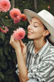 Young woman with pink flowers. lady in a hat. girl in a garden.