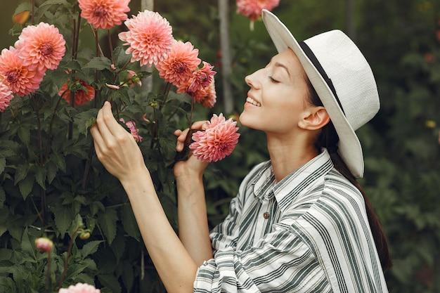 핑크 꽃과 젊은여 인. 모자에있는 여자. 정원에서 소녀입니다.