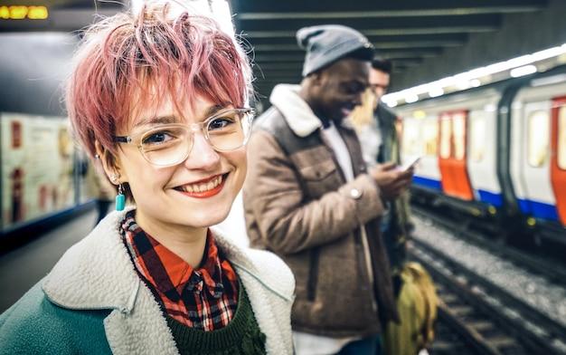 ピンクの髪の若い女性と駅で電車を待っている多民族の流行に敏感な友人のグループ