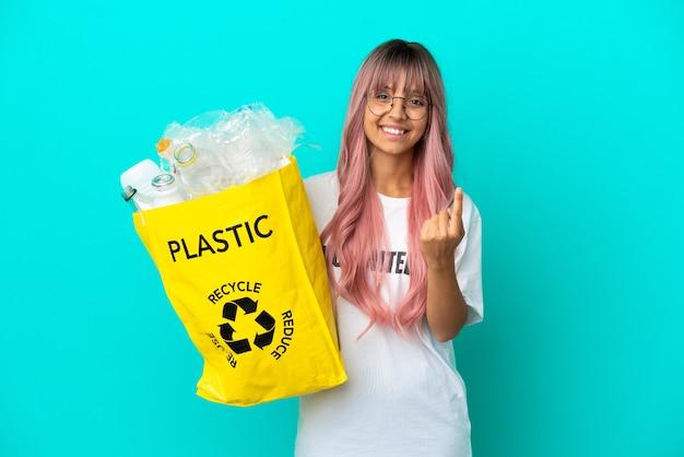 Молодая женщина с розовыми волосами держит сумку, полную пластиковых бутылок для переработки, изолированную на синем фоне, делая приближающийся жест