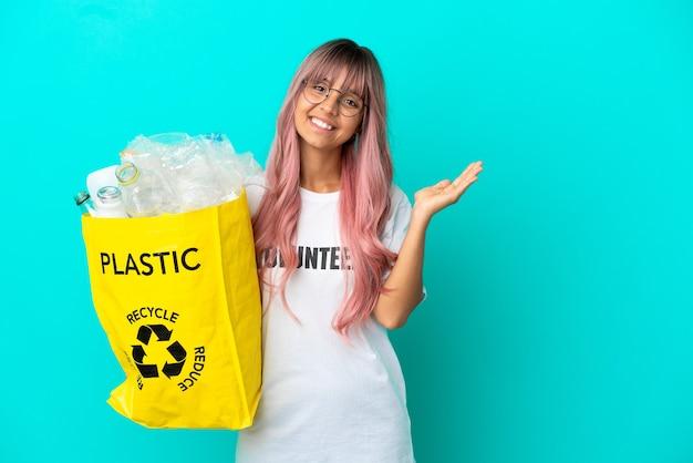 Молодая женщина с розовыми волосами держит сумку, полную пластиковых бутылок для переработки, изолирована на синем фоне, протягивая руки в сторону, приглашая приехать