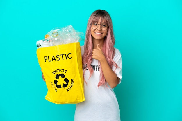 親指を立てるジェスチャーを与える青い背景で隔離のリサイクルするためにペットボトルでいっぱいのバッグを保持しているピンクの髪の若い女性