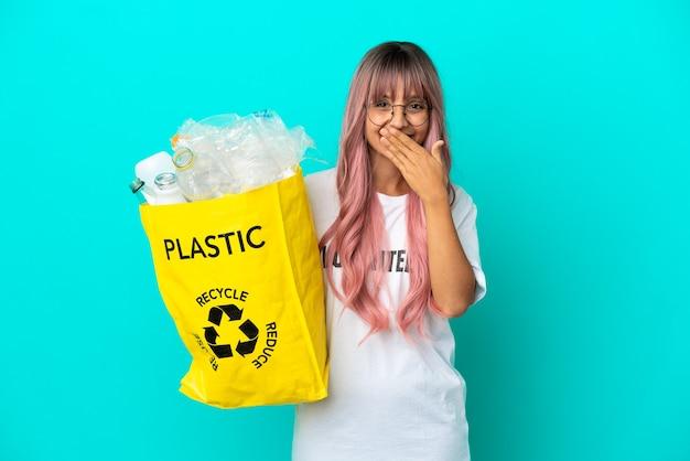 ピンクの髪の若い女性は、青い背景に分離されたリサイクルするためにペットボトルでいっぱいのバッグを持って幸せで笑顔の手で口を覆っています