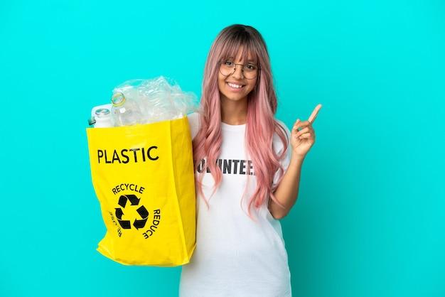 素晴らしいアイデアを指している青い背景で隔離のリサイクルするためにペットボトルでいっぱいのバッグを保持しているピンクの髪の若い女性