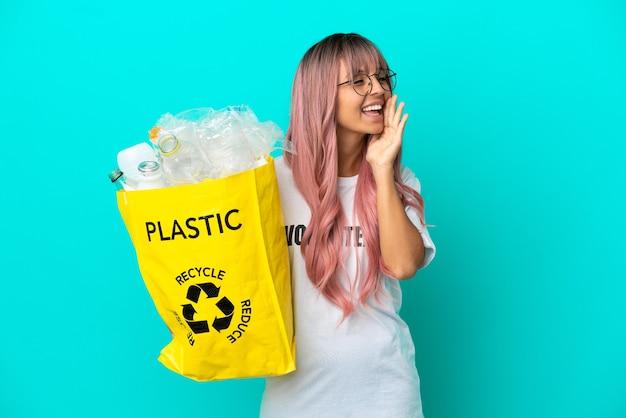 Молодая женщина с розовыми волосами, держащая мешок, полный пластиковых бутылок для переработки, изолирована на синем фоне, кричит с широко открытым ртом