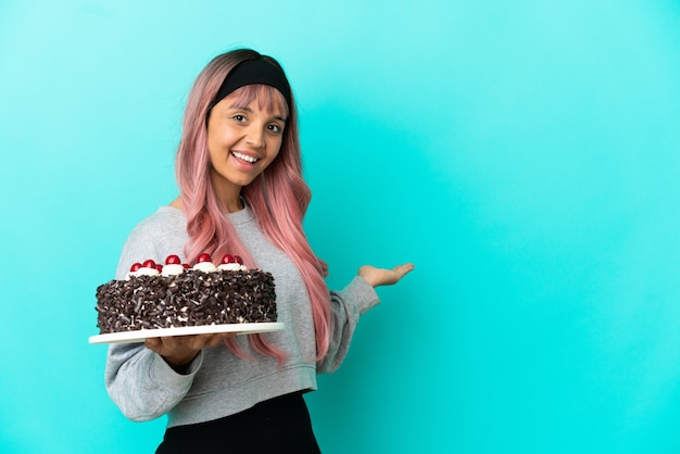 Young woman with pink hair holding birthday cake isolated on blue background extending hands to the side for inviting to come