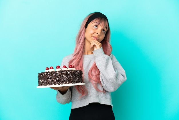 青い背景で隔離の誕生日ケーキを保持し、見上げるピンクの髪の若い女性