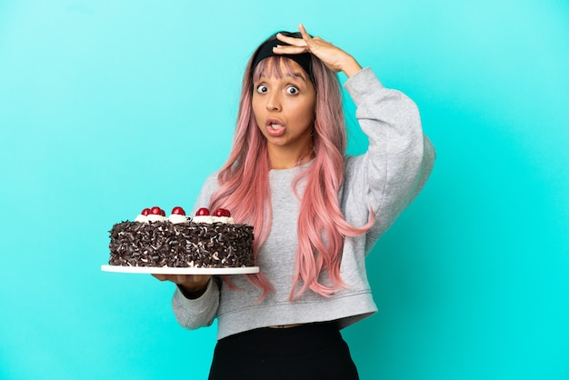横を見ながら驚きのジェスチャーをしている青い背景で隔離の誕生日ケーキを保持しているピンクの髪の若い女性