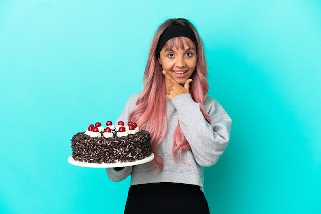 Молодая женщина с розовыми волосами держит праздничный торт на синем фоне счастлива и улыбается