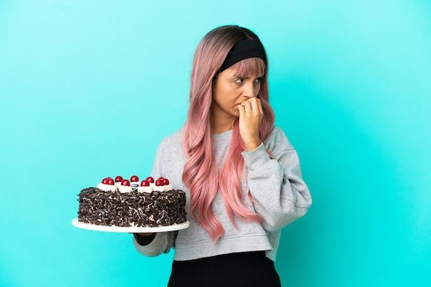 Молодая женщина с розовыми волосами держит праздничный торт на синем фоне, сомневаясь