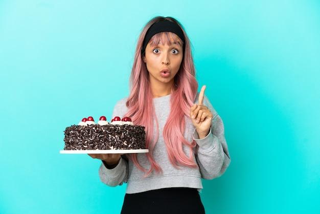 파란색 배경에 격리된 생일 케이크를 들고 분홍색 머리를 한 젊은 여성은 손가락을 들어올리면서 해결책을 실현하려고 합니다