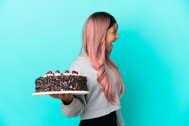 Молодая женщина с розовыми волосами держит праздничный торт на синем фоне, смеясь в боковом положении