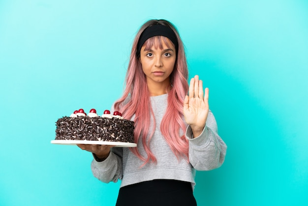 停止ジェスチャーを作る青い背景で隔離のバースデーケーキを保持しているピンクの髪の若い女性