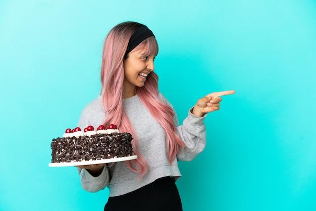 Молодая женщина с розовыми волосами держит праздничный торт на синем фоне, указывая пальцем в сторону и представляет продукт